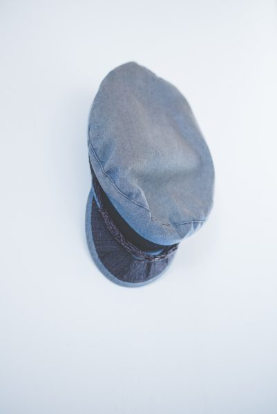 Waisted blue denim traditional hat hanging from a wall
