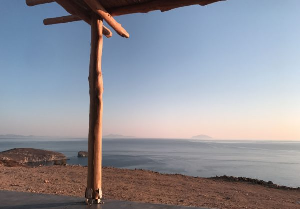 Panoramic sea view of pinkish color tones and islands' silhouettes in the horizon from a cottage with massive wooden pergola