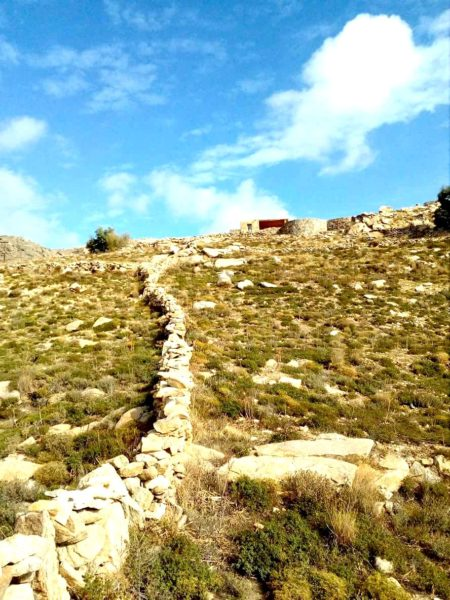 Cyclades island field in a hill with old stone walls and a small cottage with pergola in terracota tones