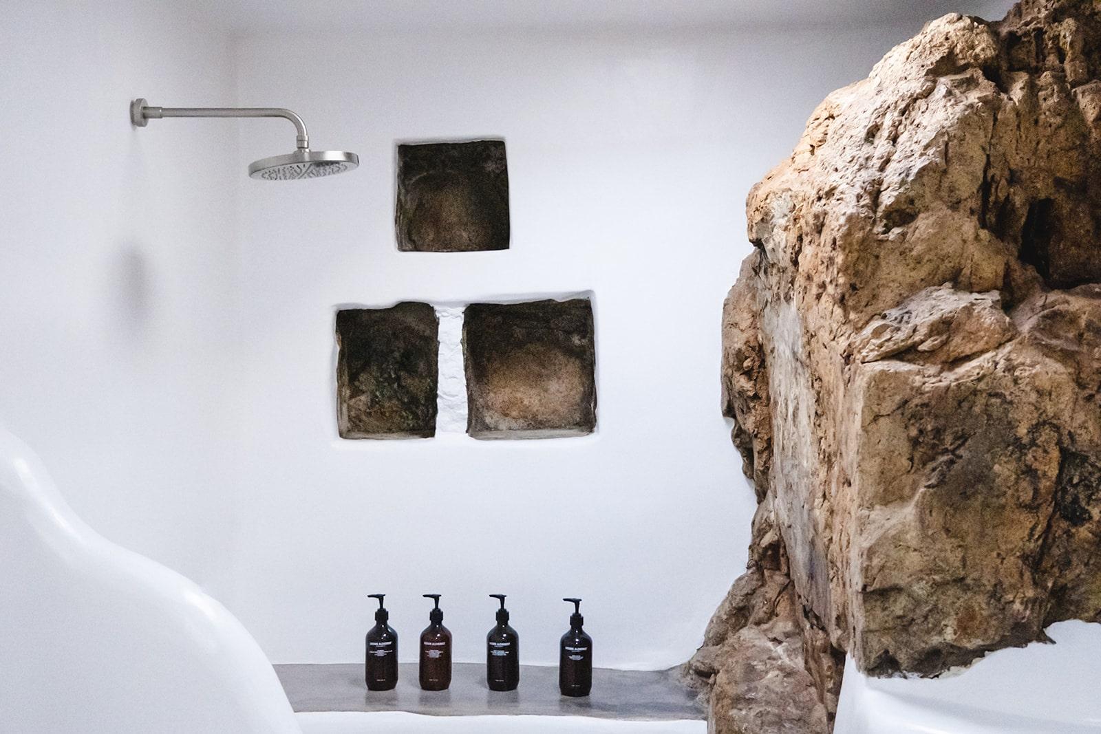 Keli Serifos bathroom with natural rock and Grown Alchemist toiletries